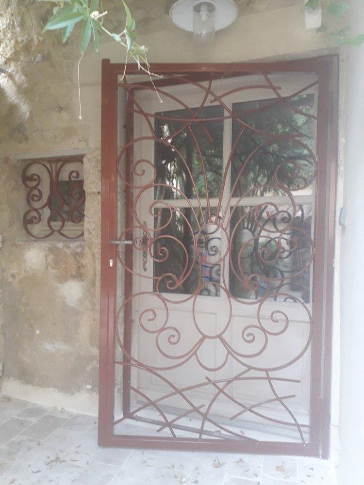 Porte en feren forme de papillon avec des grilles de défense à Bellegarde et ses environs